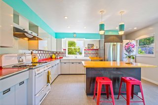 Period-appropriate lighting and bright colors keep the kitchen feeling vintage and yet contemporary.