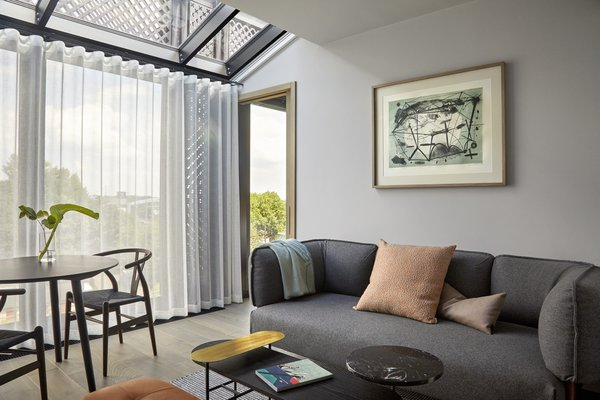 An apartment living room in the hotel features floor-to-ceiling windows and modern furniture.