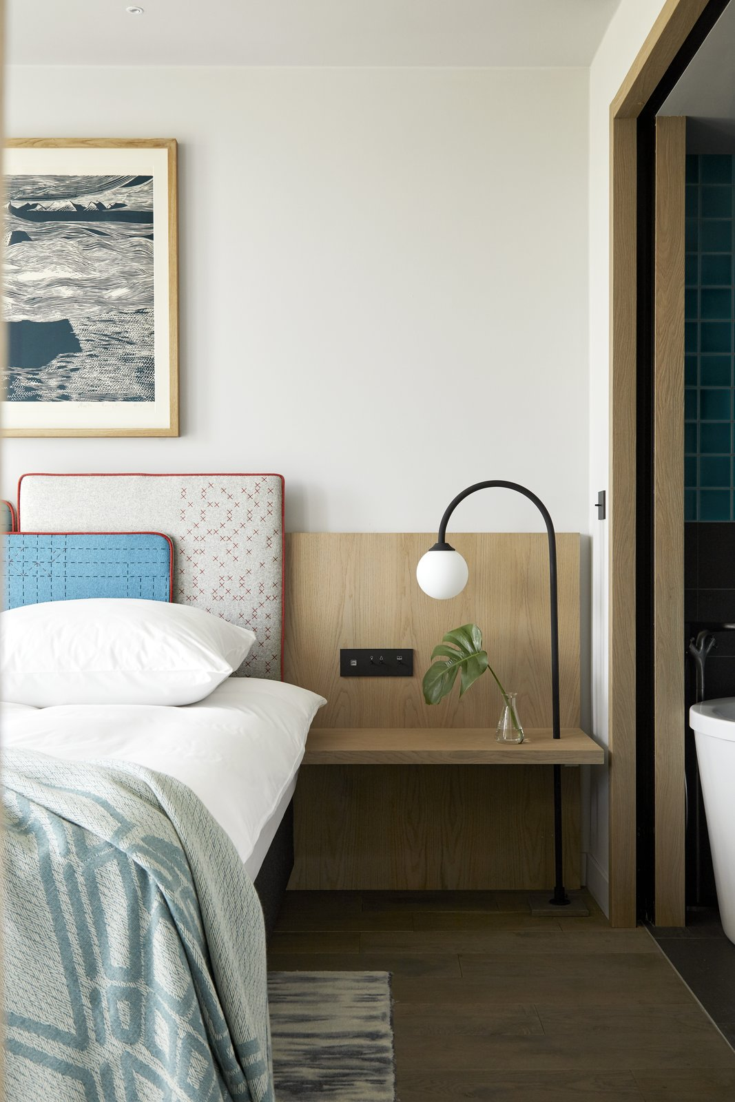 Bedroom, Bed, Rug Floor, Floor Lighting, and Night Stands An integrated headboard and bedside table in one of the hotel's bedrooms.  Best Photos from This New Hotel in Poland Is a Creative Paradise