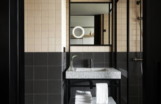 A bathroom in a guest room features a new take on traditional square two-tone tiles.