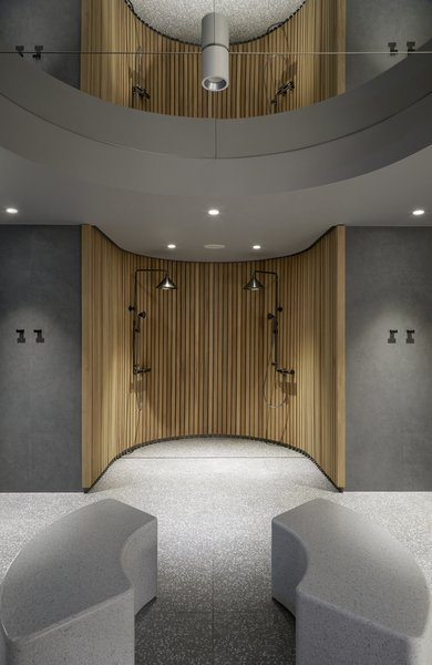 Terrazzo floors and benches are paired with an open wood shower in the hotel's sauna.