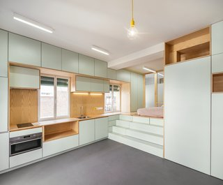 In an apartment of only about 350 square feet, Madrid–based architectural firm elii has designed a functional layout with a bright palette that emphasizes light and views to the streetscape outside. The light green cabinetry keeps the apartment feeling bright, while the wood gives texture and a natural feeling to the space.