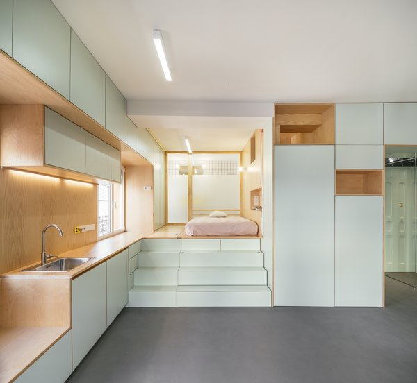 The sleeping area is raised and flush with the height of the countertops, allowing for storage underneath.