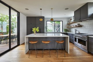 "The kitchen is kept light and bright by multiple windows and a sliding glass door, as well as white countertops and a white tile backsplash. The gray cabinets are painted in Benjamin Moore ""Kendall Charcoal"" paint in semi-gloss finish; the cabinet pulls are ""Bowman"" hardware by Rejuvenation in Oil Rubbed Bronze finish; and the wood shelves are solid live-edge oak with concealed brackets."