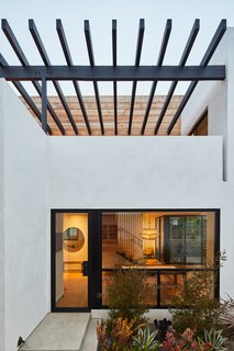 A custom steel and Douglas fir wood trellis provides some relief from the strong California sun, which bounces off the white walls. The trellis is stained with a custom color.