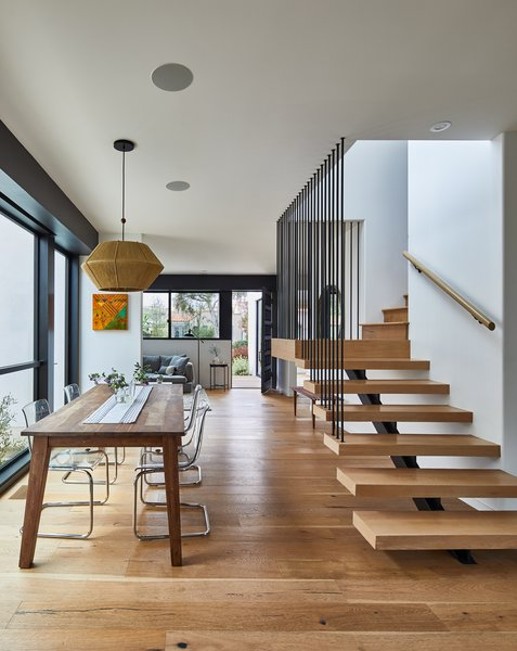 Wide-planked white oak wood flooring is echoed in both the wooden dining table and the floating wood treads of the stairs leading to the second floor.