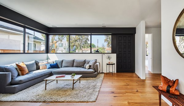 """The main living space on the ground floor is located directly off the front door. It has a long horizontal window on two sides. The custom wood door is painted in Farrow & Ball """"Pitch Black"""" with Emtek """"Davos Tubular Marmont"""" mortise hardware and a US Black finish."""