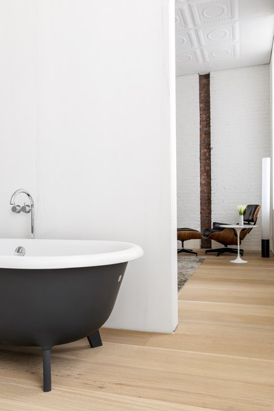 The main bathroom, with its black-and-white stand-alone tub, can be closed off with sliding doors.