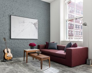 The burgundy sofa mirrors the brick facade outside, providing a moment of color against the otherwise neutral colors.