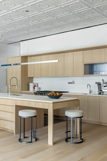 The open-layout kitchen blends into the dining area and living space. Andrew Berman renovated the kitchen, but interior designer Justin Charette provided the styling and accessories.