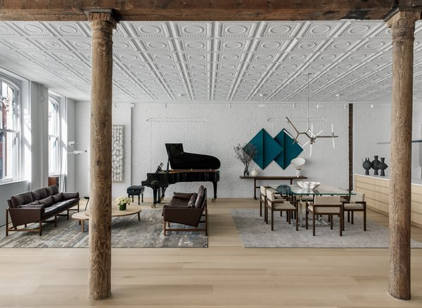 After architect Andrew Berman renovated a 2,800-square-foot, two-bedroom SoHo loft, designer Justin Charette fitted out the interior with minimalist furnishings and built-ins to complement the landmark building's industrial and historical features—including a pressed tin ceiling and exposed wood beams. Designed as a pied-à-terre for a bicoastal client, the converted loft retains its high ceilings and tall windows that flood the open-plan interior with natural light while introducing a more streamlined aesthetic that includes a neutral palette of white oak, exposed brick walls painted white, and sleek contemporary furnishings—many of which were sourced from local New York designers and makers.