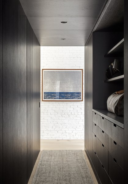 In contrast to the natural white oak millwork found in the living areas, the owner's private closet storage is stained in a dark color.