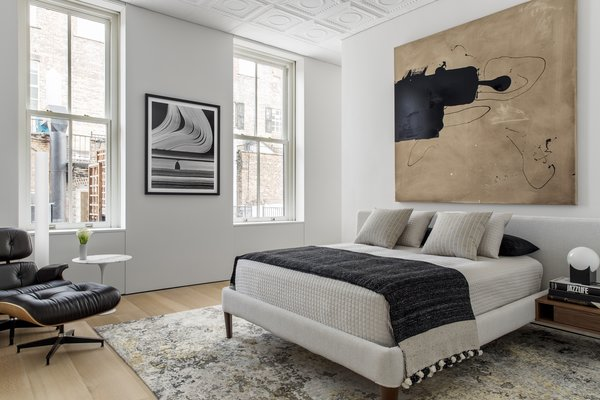 One of the two bedrooms has simple furnishings and thoughtfully placed artwork, all in neutral tones made lively with texture and pattern.