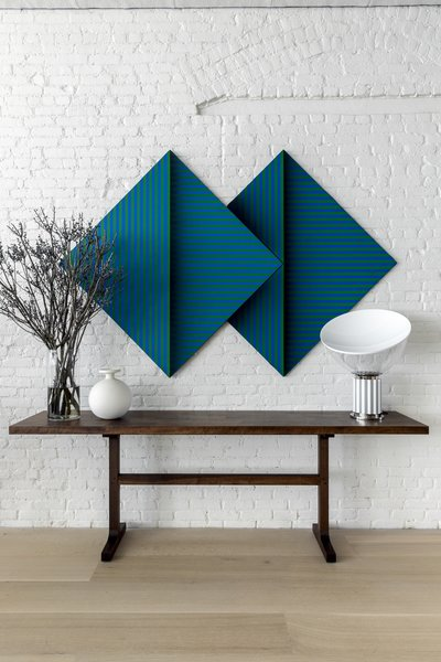A bold green and blue artwork is posed above a dark wood trestle table in the dining area.