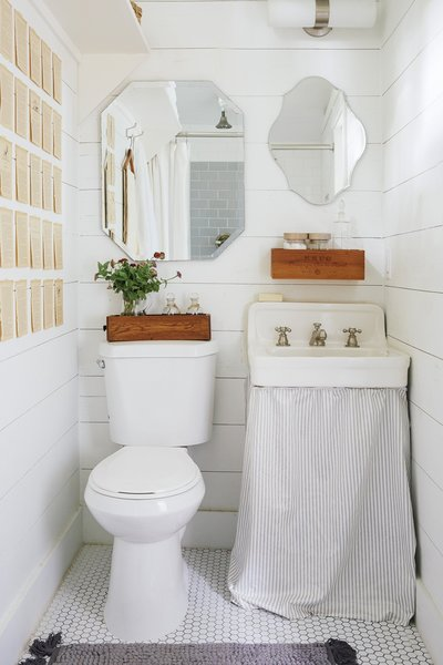 In search of a home office for designer Paige Morse, she looked to two existing sheds in her own backyard and transformed them into a workspace complete with a small bathroom. The walls, floor, and tile floor are all white, including a vintage white sink.