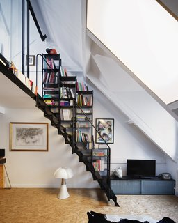 A black steel staircase with integrated storage leads up to a lofted bedroom