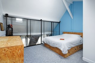 Architect Florent Chagny renovated the top floor of an 1830s building in Paris with OSB, black steel, and a splash of bright blue.