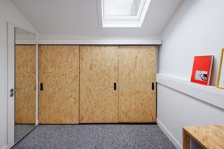 The bedroom closet features sliding oriented strand board doors and black hardware.