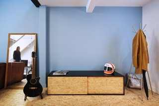 A bright blue feature wall strikes contrast with the texture and color of the oriented strand board and black surfaces. The storage piece is custom-made.