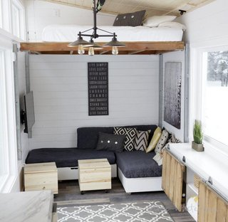 At one end of the tiny home is the living area, with seating on casters for mobility and a lofted bed. Storage has sliding doors for access and covers the wheel well; the leaves of the cabinet can also be flipped horizontally to create a table. The lofted bed can be lowered with the push of a button, and a coffee table doubles as a step stool.
