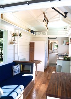 The use of light colors on the walls and ceiling of The Pacific Pioneer by Handcrafted Movement keeps the two lofted sleeping spaces at either end of the tiny home from feeling claustrophobic, while the blues, greens, and natural wood of the furniture and cabinetry are simple but thoughtful.