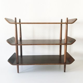 Designed and produced in the Netherlands in 1953, this teak standing shelf could function as either a bookcase or a sideboard in a dining room or living room. The four teak posts are tapered at both the top and the bottom, and the ends of each shelf are turned upwards, exhibiting the bendable properties of plywood. We could see this simple but elegant piece in just about any room!