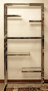 This chrome and glass etagere, or standing open shelving unit, was designed in the 1970s by famous furniture designer Milo Baughman. The etagere features four intermediate floating shelves and a central full-length shelf for bracing. The clear glass and reflective chrome make for a fun play on light.