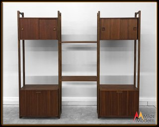 This tripartite walnut unit provides a great mix of open shelving, pull-out drawers, and sliding doors for everything from books and nicknacks to messier items that you want to keep out of sight. The vertically-oriented walnut panels on the bottom drawers keep the piece from feeling too heavy, and the carved walnut handles are particularly lovely.