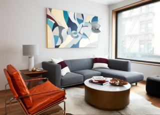 At an apartment in Brooklyn, New York, interior designer Kesha Franklin of Halden Interiors uses a mixture of neutral grays and blues in the living room with punches of deep reds and a leather chair for texture.