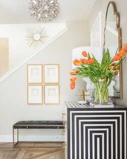 A boldly patterned black-and-white cabinet is the star of this stair hall and entryway, which has accents of rich golds that shine against a neutral taupe wall. Sculptural light fixtures also help give the space a sense of personality and richness.