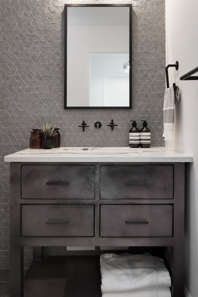 Textured accent walls, masculine metals, and wall-mounted fixtures create a spa-like retreat for a classic gentleman's bathroom designed by Eneia White Interiors.