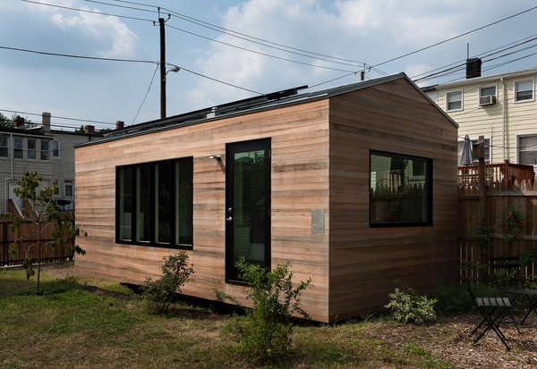 The home has rooftop solar panels, and it's clad with cypress wood that turns a light gray over time.