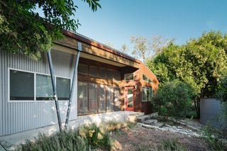 The exterior of the home features corrugated metal, wood siding, and weathered steel panels. A V-shaped column helps hold up the front porch.