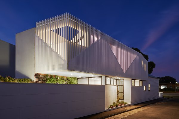 At night, the battens on the facade glow, further emphasizing the triangular shapes inspired by the gabled roofs of the home and its neighbors.
