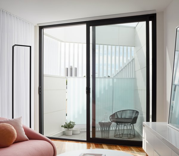 A small terrace on the second floor is partially enclosed with battens and polycarbonate for privacy, but the spacing of the battens and the translucency of the polycarbonate still allow for light and views of the city beyond.