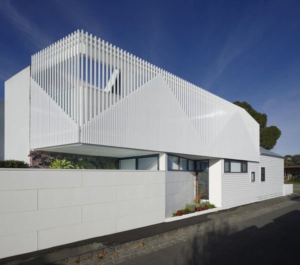 The street wall, new addition, and existing building are all united in their color palette of shades of white, but are distinct in their materials, shape, and joint patterns. The street wall and existing building have a horizontal emphasis, while the second floor's addition has a vertical one.