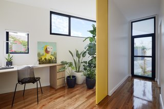 A large sliding door closes off a small home office, which takes advantage of its irregular shape by placing windows and plants near the corner.