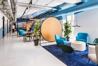 Exposed ductwork gives the interiors an industrial edge, while colorful painted geometric forms add a lively, dynamic look. Plush seating in bright blues and greens keeps the space feeling fun and youthful.