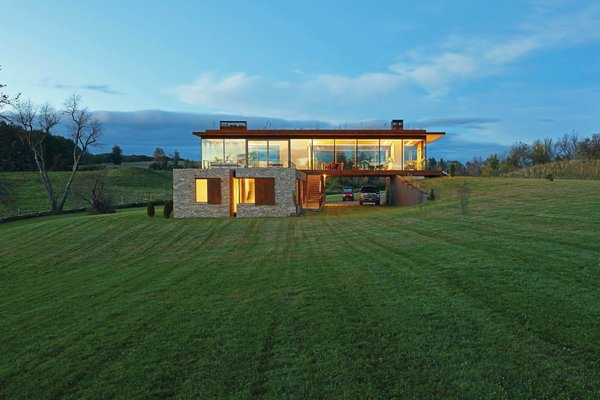 The home's two volumes are distinct not only in their orientation, but also in their materiality. The lower level is wrapped in stone, while the upper level is composed of glass.