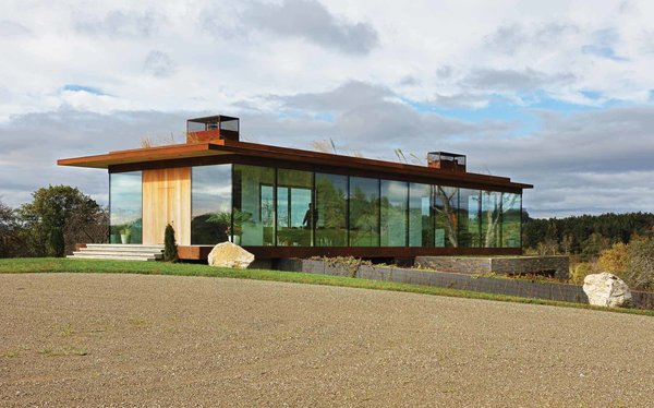 The upper floor is wrapped in glass, with the exception of the solid wood front door and the cantilevering roof.