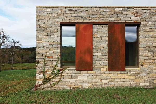 The lower level is clad in locally sourced stone. The punched windows feature weathered steel accents.