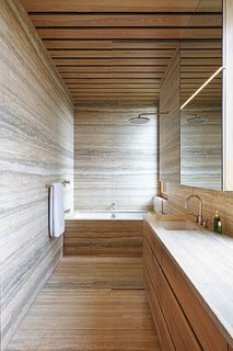 The lower-level master bath matches horizontally oriented stone with wood cabinets and drawers made from on-site trees.