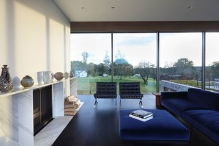 The glass second floor allows for views through the residence to the bucolic landscape beyond.