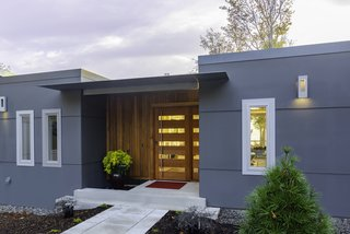The main entry is denoted by a change in material from the facade's gray metal panels: vertically oriented wood boards and a glass-and-wood front door. The entry leads into the main hallway, whose strategically placed skylights bring in plenty of natural light.