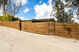 On the street-facing side, the home has a privacy fence made from wood and weathered steel.