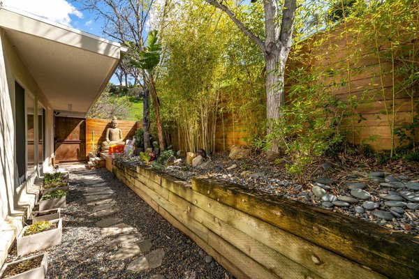 The side yard features a Zen garden with local plantings, and an area that is partially covered by a cantilevering roof.