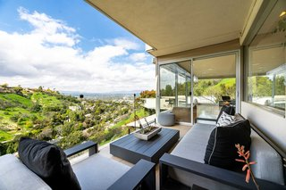 A glass guardrail on the outdoor terrace provides uninterrupted views of the valley below.