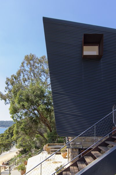 The home's punched windows are shaded by Cor-Ten steel.