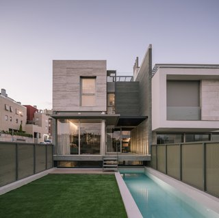 The rear of the house continues the same mix of materials as the front facade and includes a long, narrow pool.