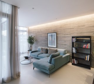 The home's furniture and window treatments complement the neutral tones of the exterior and interior materials. Textured walls of board-formed concrete provide visual interest in the living room.